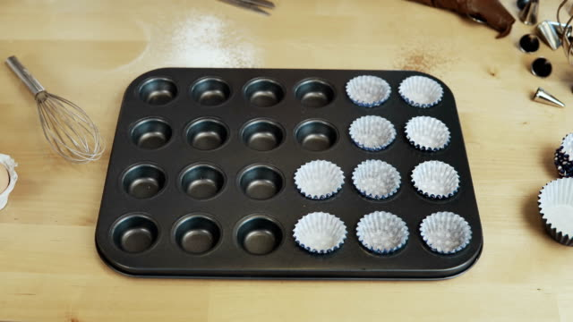 Stop-motion-Paper-cups-wrappers-for-cupcakes-putting-into-the-baking-tray-for-muffins-Cooking-in-the-kitchen