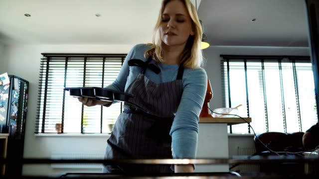 View-inside:-young-beautiful-woman-opens-the-oven-and-puts-in-the-baking-tray-with-cupcakes-Female-cooking-at-home