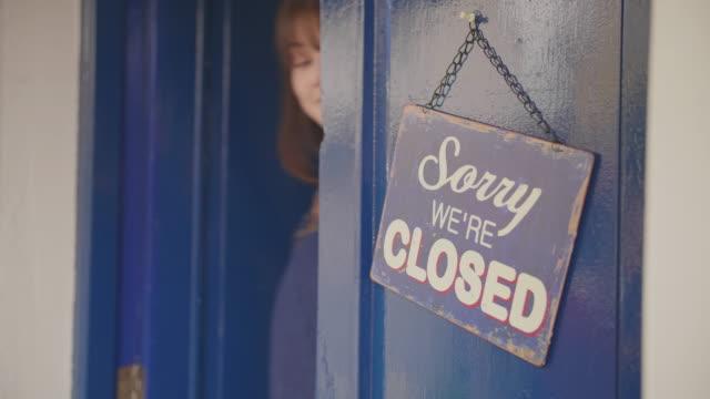 Propietario-de-Deli-convirtiendo-señal-de-abierto-a-cerrado-en-la-puerta
