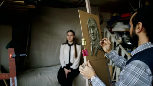 Creación-de-escultura-de-la-cara-del-ser-humano-en-la-lona-mientras-el-joven-le-posando-en-estudio-de-arte-de-escultor