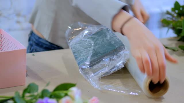 Floreria-envuelve-la-espuma-floral-en-film-transparente-para-arreglo-de-flores-en-floristeria