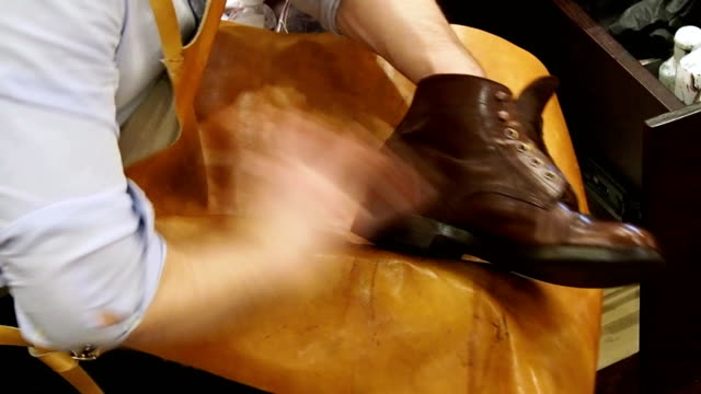Shoe-shiner-polishes-the-boots-of-brown-leather-with-a-special-brush