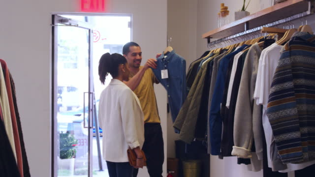 Young-Hispanic-couple-looking-at-clothes-in-a-clothes-shop