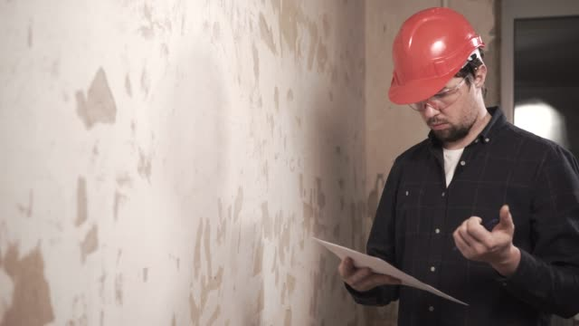 Builder-in-a-protective-glasses-and-a-hat-watching-the-flat-