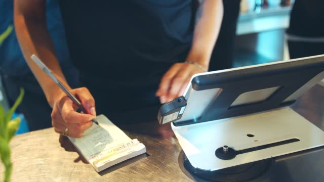 Close-Up-Of-Waitress-Totaling-Bill-At-Coffee-Shop-Checkout