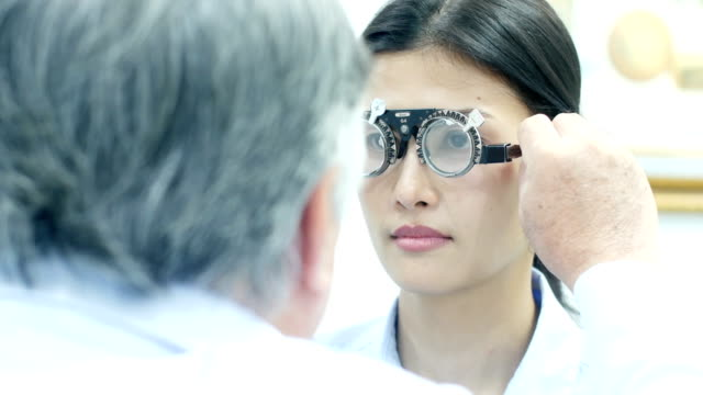 Asian-woman-test-eye-glass-at-clinic-People-with-healthcare-and-medical-concept-
