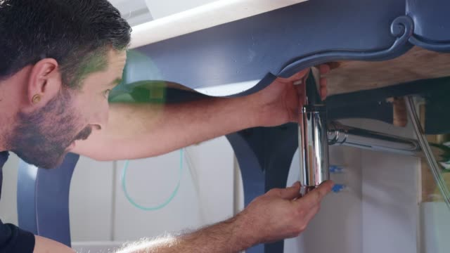 Plumber-Fitting-New-Waste-Trap-To-Wash-Basin-In-Bathroom