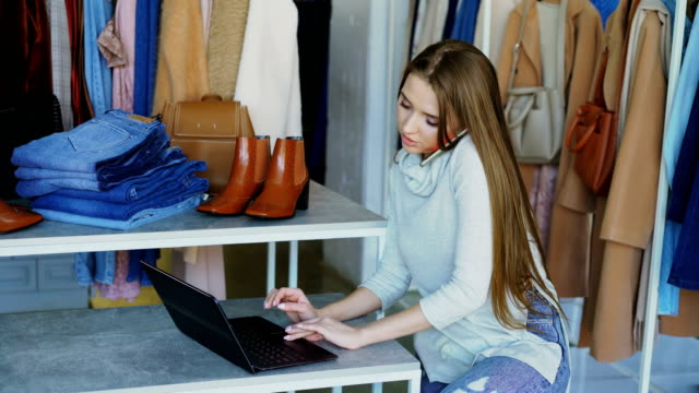 Attractive-young-businesswoman-is-sitting-and-talking-on-mobile-phone-while-working-with-laptop-in-her-clothing-store-Trendy-garments-shoes-and-bags-in-background-