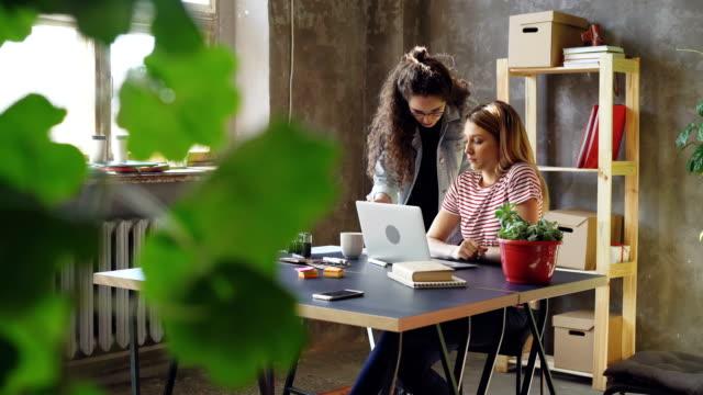 Jóvenes-propietarios-de-pequeñas-empresas-están-trabajando-con-el-portátil-en-la-oficina-de-estilo-moderno-loft-Rubia-está-sentada-y-escribiendo-morena-es-permanente-y-sugiriendo-ideas-