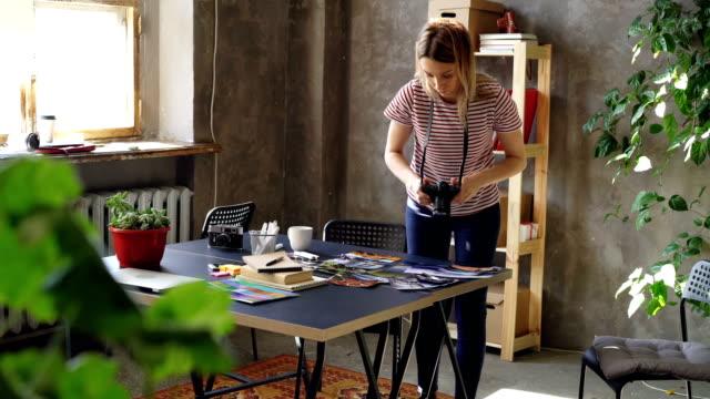 Junge-kreatives-Mädchen-macht-lag-flach-aus-bunten-Fotos-dann-schießen-sie-mit-Kamera-Frau-steht-in-der-Nähe-von-moderner-Tisch-und-lockere-Kleidung-zu-tragen-