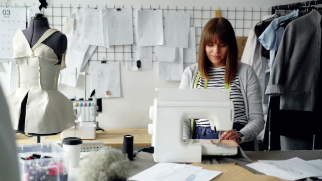 Professional-female-tailor-is-adjusting-sewing-machine-then-stitching-pieces-of-fabric-Woman-is-working-in-light-tailoring-studio-Sewing-items-and-mannequins-are-visible-