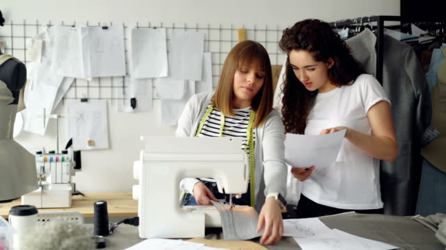 Attractive-dressmakers-are-looking-at-sketches-and-working-with-sewing-machine-then-checking-stitches-and-adjusting-equipment-Professional-teamwork-concept-