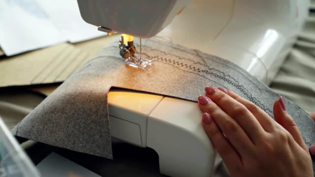 Tiro-de-Close-up-de-máquina-de-coser-tela-y-mano-femenina-cuidado-de-trabajo-Concepto-de-proceso-de-fabricación-de-ropa-Colores-luz