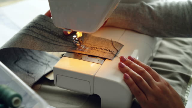 Close-up-view-of-modern-electric-sewing-machine-working-stitching-piece-of-fabric-Girl-s-manicured-hand-and-colorful-sewing-threads-are-visible-