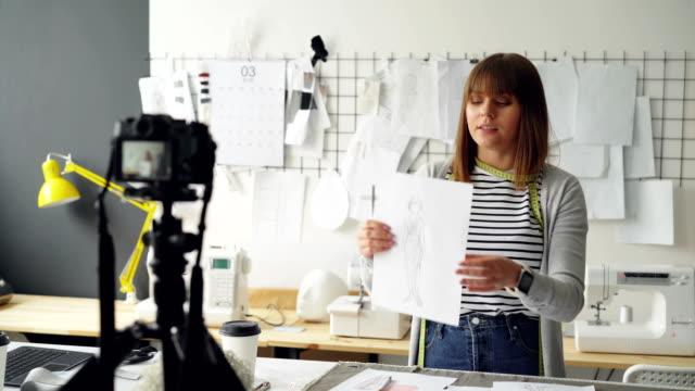 Blogger-creativo-está-grabando-video-de-su-nueva-colección-de-ropa-con-cámara-Mostrando-el-boceto-y-hablar-de-ella-emocionalmente-para-el-videoblog-