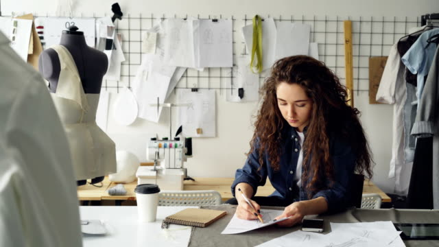 Young-woman-fashion-designer-is-drawing-ladies-garment-sketch-at-desk-in-modern-workshop-Mannequin-sewing-items-to-go-coffee-are-visible-