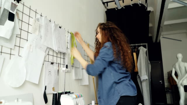 Low-angle-view-of-young-fashion-designer-looking-at-sketches-and-hanging-drawings-on-wall-in-modern-loft-style-studio-Large-collection-of-illustration-above-tailoring-desk-