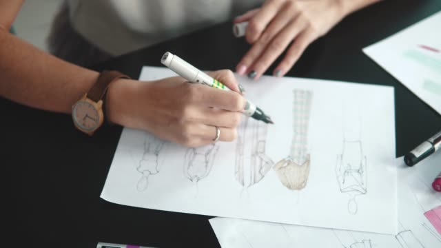 designer-of-clothes-makes-an-outline-of-clothes-with-a-felt-tip-pen-female-hands-closeup