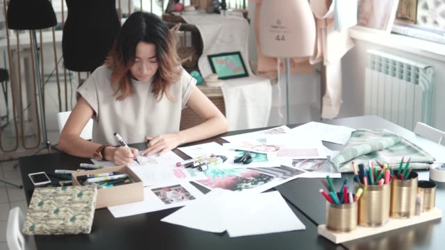 designer-of-clothes-makes-a-sketch-of-clothes-in-a-sewing-workshop-a-girl-working-for-herself-is-busy-with-creative-work