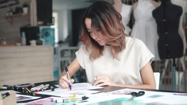 diseñador-de-ropa-hace-un-bosquejo-de-la-ropa-en-un-taller-de-costura-una-chica-que-trabaja-para-sí-misma-está-ocupada-con-el-trabajo-creativo