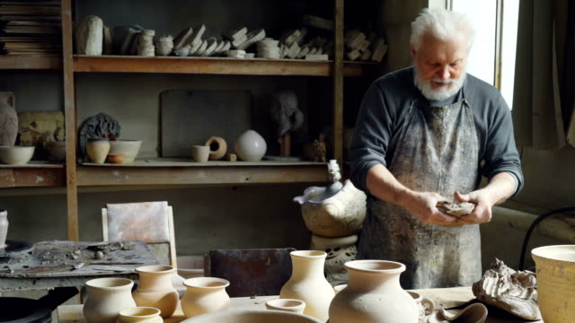 Professional-male-ceramist-is-kneading-clay-forming-clay-ball-while-working-in-small-workshop-with-potter-s-equipment-tools-and-many-ceramic-figures-