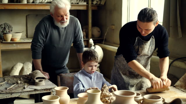 Professional-potter-is-kneading-clay-on-worktable-in-home-studio-while-his-son-is-helping-him-and-his-elderly-father-watching-them-from-behind-Small-family-business-concept-