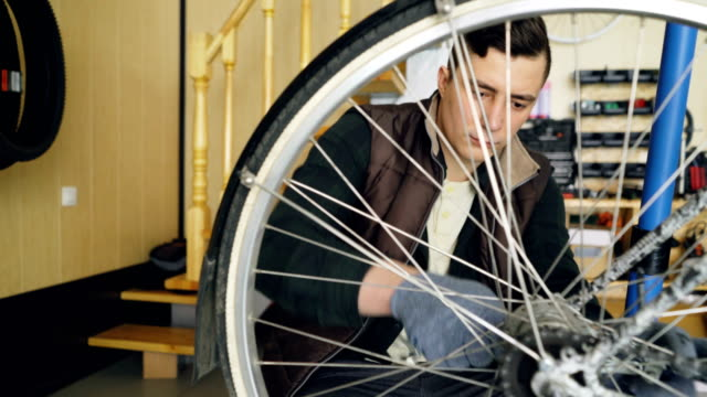 Young-man-experienced-serviceman-is-fixing-bike-wheel-using-wrench-and-tools-Small-cozy-workshop-interior-with-wooden-walls-and-ladder-spare-parts-and-equipment-are-visible-