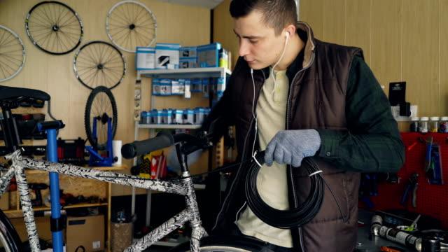 Joven-dueño-mecánico-de-bicicletas-reparacion-taller-está-reparando-bicicletas-manteniendo-el-haz-de-cables-y-fijación-al-marco-de-la-bici-Pequeños-negocios-y-mantenimiento-concepto-
