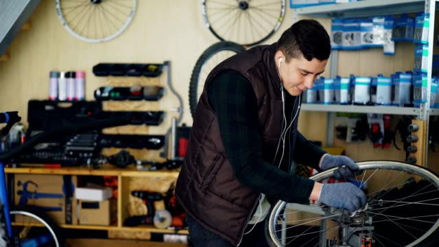 Apuesto-mecánico-es-limpieza-de-rueda-de-bicicleta-de-exterior-e-interior-hub-y-con-pedazo-de-tela-y-escuchando-música-con-auriculares-Concepto-de-profesión-y-personas-