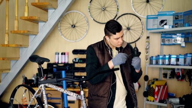 Concentrado-reparador-es-engrasar-mecanismo-y-reparación-de-bicicletas-en-taller-agradable-Joven-caliente-chaleco-y-guantes-de-protección-es-escuchar-música-