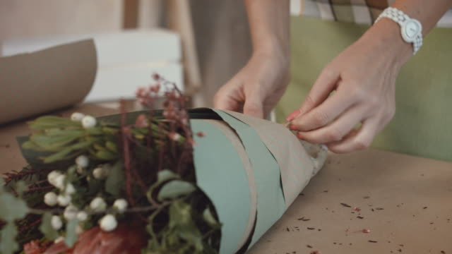 Florist-packing-festive-bouquet-in-wrapping-paper
