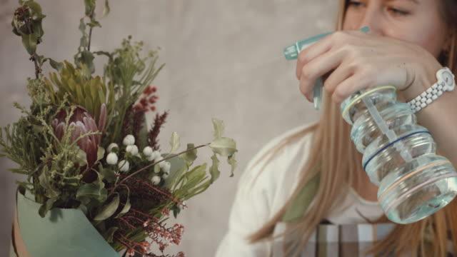 Florist-watering-flower-bouquet-arrangement
