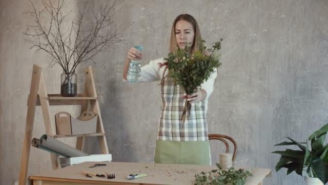 Florist-watering-flower-bouquet-at-flower-shop