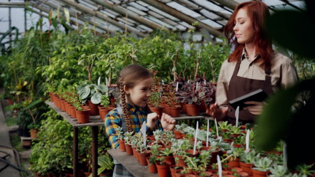 Young-woman-gardener-in-apron-and-her-daughter-are-dancing-in-greenhouse-having-fun-woman-is-holding-tablet-Happy-family-gardening-parents-and-children-concept-