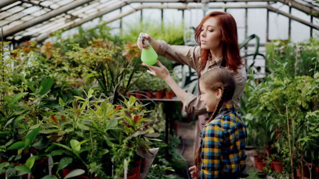 Cheerful-female-gardener-is-sprinkling-water-on-plants-and-having-fun-with-her-adorable-little-daughter-Growing-flowers-people-and-family-concept-