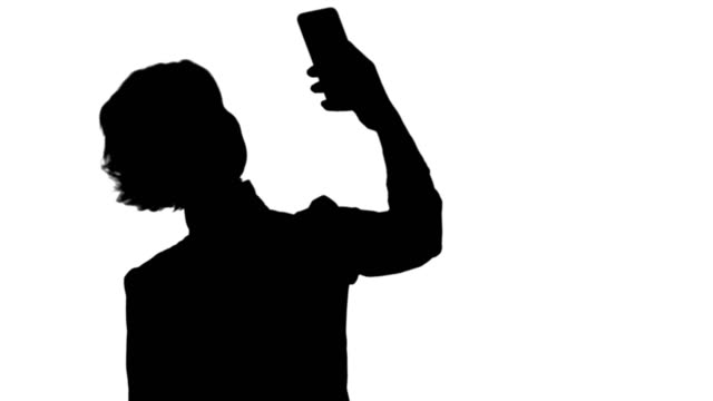 Silhouette-Businesswoman-taking-funny-selfie-with-phone-track-matte