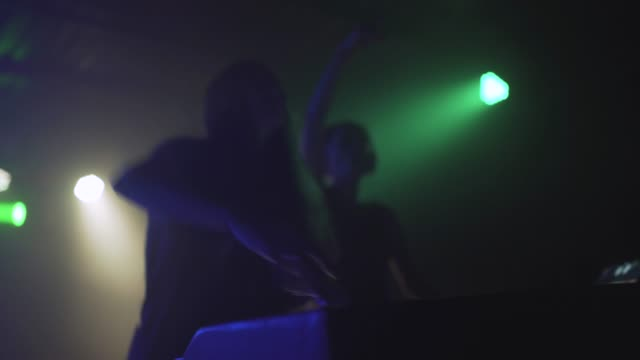 Two-beautiful-young-women-DJ-play-the-music-on-the-mixing-console-in-the-nightclub