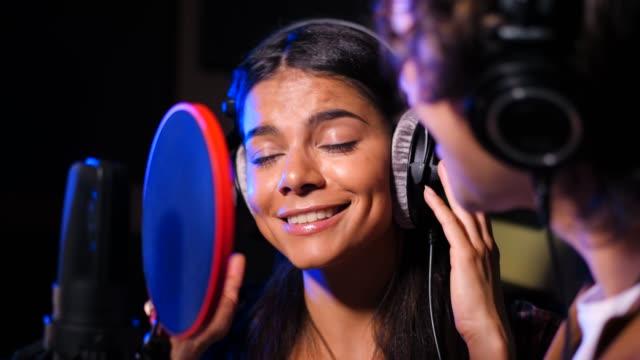 Zwei-junge-Sängerinnen-und-Sänger-ihren-Song-im-Tonstudio-durchführen-Professioneller-Musiker-Duo-Aufnahme-neue-Album-CD-Schönes-Paar-zusammen-arbeiten-Slow-Motion-4k