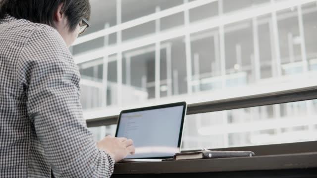 Hombre-de-negocios-asiático-joven-usando-la-computadora-portátil-en-el-espacio-de-trabajo-con-el-smartphone-y-el-portátil-en-el-escritorio-de-madera-Macho-mano-escribiendo-en-el-teclado-del-ordenador-portátil-Estilo-de-vida-independiente-en-concepto-