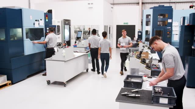 Taller-de-ingeniería-ocupado-con-trabajadores-con-maquinaria-CNC