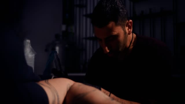 Professional-skilled-tattoo-master-making-tattoo-design-on-client-s-skin
