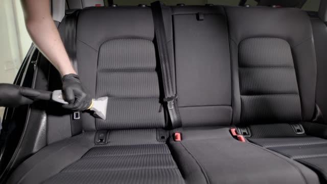Faceless-employee-carefully-vacuuming-car-seat