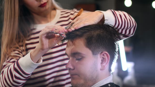 Close-up-master-hairdresser-does-hairstyle-and-style-with-scissors-and-comb-Concept-Barbershop