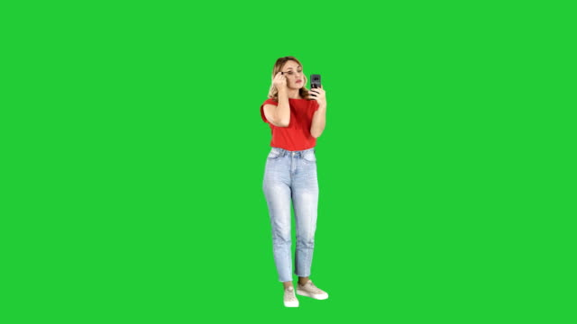Beautiful-young-woman-using-mascara-and-looking-in-her-smartphone-on-a-Green-Screen-Chroma-Key