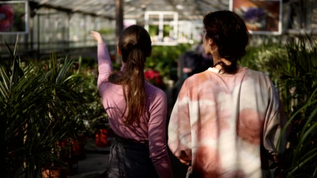 Back-view-of-young-female-florist-walking-with-a-client-and-showing-her-different-plants-explaining-information-Young-woman-is-listening-carefully-to-the-florist