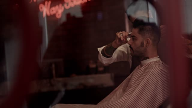 Man-getting-haircut-by-stylish-barber-in-old-fashioned-barber-shop