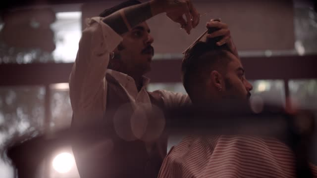 Young-stylish-barber-cutting-man-s-hair-in-vintage-barber-shop