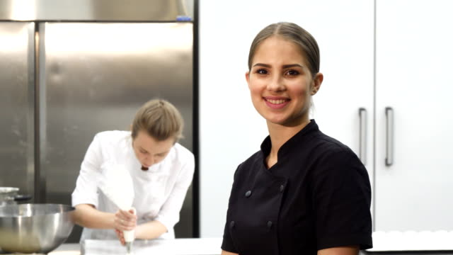 Happy-female-chef-smiling-showing-thumbs-up-at-the-kitchen