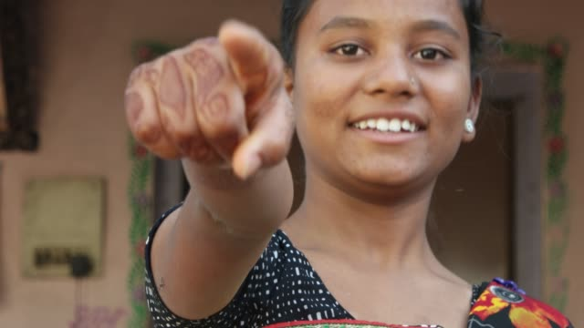 Mid-shot-of-young-beautiful-Indian-woman-points-finger-best-of-luck-good-choice-approval-accept-selected-at-camera-with-her-henna-tattoo-hand-smiling-positive-confident-leader-conviction-static-shot
