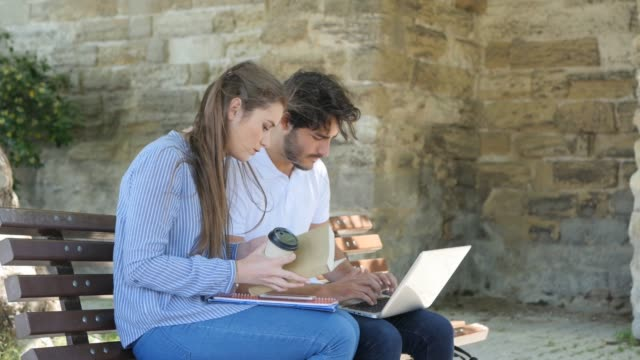 couple-of-young-students-man-and-woman-working-together-with-laptop-computer-outdoor-in-a-street-during-summer